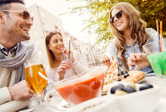 Friends eating pizza. Young group of laughing people eating pizza and having fun.They are enjoying eating and drinking together Stock Image
