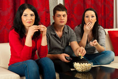 Friends eating popcorn at movie Stock Image