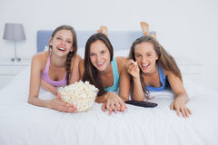 Friends eating popcorn and watching tv. On bed in their pajamas Stock Images