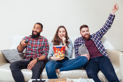 Friends eating popcorn and watching tv together Stock Photo