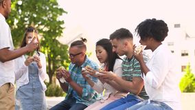 Friends eating sandwiches and talking in park stock video footage