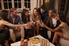 Friends Eating Snacks As They Celebrate At Party Together Royalty Free Stock Photos
