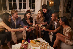 Friends Eating Snacks As They Celebrate At Party Together Royalty Free Stock Images