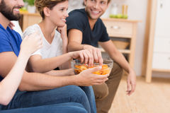 Friends eating snacks while watching television Royalty Free Stock Photography
