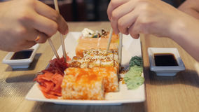 Friends eating sushi rolls in japan restaurant. Royalty Free Stock Photos