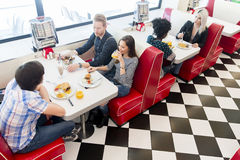 Friends eating at the table in the diner. Young friends eating at the table in the diner Stock Photos