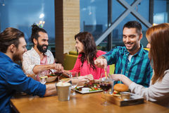 Friends eating and tasting food at restaurant Royalty Free Stock Photography