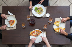 Friends Eating Together. Top view of friends eating pizza and salad on a woooden table in a restaurant Stock Images