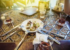 Friends eating Turkish baklava in cafe. Friends eating Turkish baklava and Turkish tea in traditional Turkish cafe on a sunny day Royalty Free Stock Photo