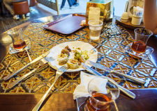 Friends eating Turkish baklava. And Turkis tea in traditional Turkish cafe Royalty Free Stock Photo