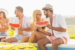 Friends eating watermelon by the pool. Group of friends at a poolside summer party, sitting at the edge of a swimming pool, eating cold watermelon slices and royalty free stock photos