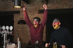 Friends emotionally watching soccer game in sport bar. Cheerful German friends with coloured faces emotionally watching soccer game in sport bar. Holiday Stock Images