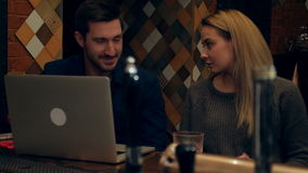 Friends ending online conference via laptop in a bar stock footage
