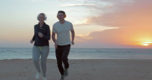 Friends Engaged in Sports. Steadicam shot of two friends jogging on the beach. Setting sun is shining upon their backs stock video footage