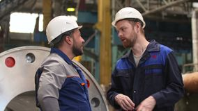 Friends engineers meet in industry plant and discuss plans.  stock footage