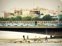 Friends enjoy Isfahan riverside under city skyline and bridges Royalty Free Stock Image
