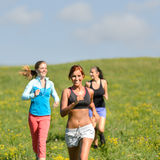 Friends enjoy running through sunny meadow. Smiling Royalty Free Stock Image