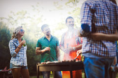 Friends enjoying bbq party. Friends having fun grilling meat enjoying bbq party Royalty Free Stock Images