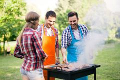 Friends enjoying bbq party in a park and smiling. Friends having fun grilling meat enjoying bbq party royalty free stock photography