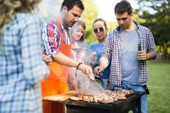 Friends enjoying bbq party and smiling in nature royalty free stock photos