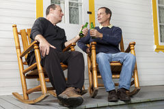 Friends enjoying a beer. On their front porch Royalty Free Stock Image