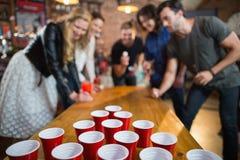 Friends enjoying beer pong game in bar. Friends enjoying beer pong game on table in bar Stock Image