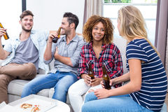 Friends enjoying beer while sitting on sofa at home Stock Photography