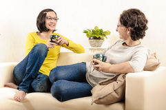 Friends enjoying coffee home chat happy faces Stock Images