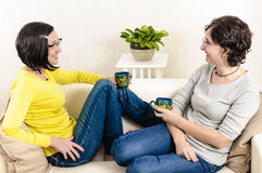 Friends enjoying coffee home chat Royalty Free Stock Images