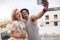 Friends enjoying drinks during rooftop party Stock Images
