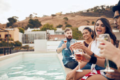 Friends enjoying drinks during rooftop party Royalty Free Stock Images