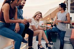 Friends enjoying drinks during rooftop party Stock Photos