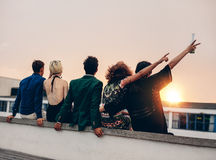 Friends enjoying drinks on rooftop at sunset Royalty Free Stock Images