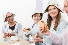 Friends enjoying the fast food at new house. Happy friends wearing workwear and paper hat enjoying the fast food at new house stock photos