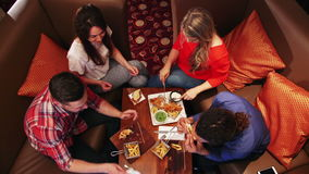 Friends Enjoying Food. Aerial view of a group of friends eating at a restaurant. They are talking and sharing their food stock footage