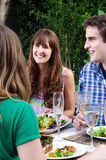 Friends enjoying food and drinks at a gathering Royalty Free Stock Images