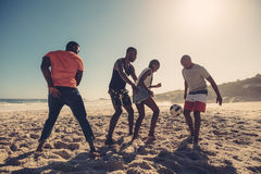 Friends enjoying a game of soccer at beach Royalty Free Stock Photography