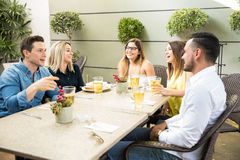 Friends enjoying happy hour. Wide view of a group of young adults drinking some beers during happy hour in a restaurant and having fun Stock Photos