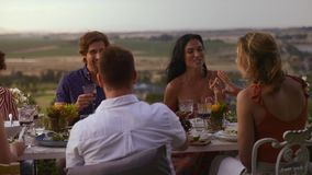 Friends enjoying having dinner togehter. Smiling group of friends eating food and talking at dinner party. Cheerful people enjoying having food togehter at a stock video footage
