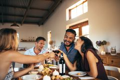 Friends enjoying home party with drinks and jokes Royalty Free Stock Photos