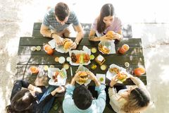 Friends Enjoying Junk Food At Table. Directly above shot of men and women having junk food at restaurant stock images
