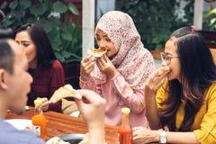 Friends Enjoying Meal In Outdoor Restaurant Stock Image