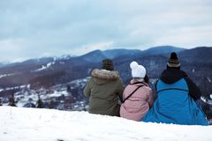 Friends enjoying mountain landscape, space for text. Winter vacation stock photo