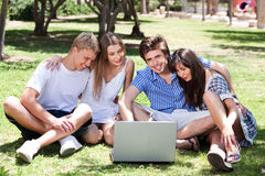 Friends enjoying movie in park on laptop royalty free stock photo