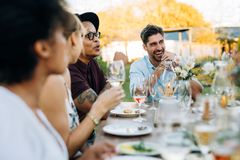 Friends enjoying outdoor summer meal. Young men laughing while sitting with friends at outdoors party. Friends enjoying summer meal at outdoor restaurant royalty free stock images