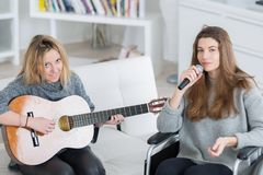 Friends enjoying playing guitar and singing together. Teen royalty free stock photos