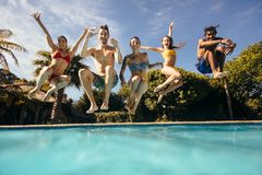 Friends enjoying pool party. Group of multi-ethnic young people looking happy while jumping into the swimming pool together. Friends enjoying pool party Stock Images
