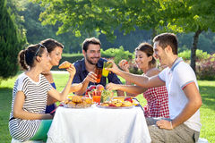 Friends enjoying a relaxing picnic. Sitting together laughing and chatting at a table in a lush green park Royalty Free Stock Images