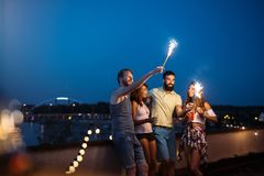 Friends enjoying a rooftop party and dancing with sparklers. In hands Stock Photo
