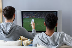 Friends enjoying soccer in TV. Fans of same game. Rear view of guy sitting on couch and watching football with his friend, holding remote in hand Royalty Free Stock Images
